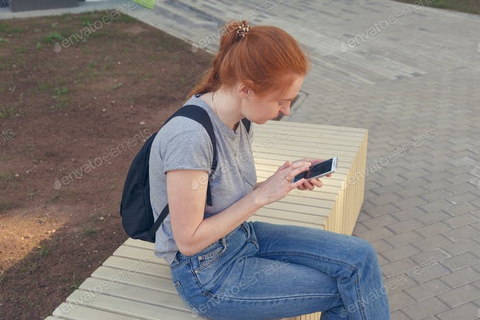 joven Mujer hipster pelirroja Uso teléfono.