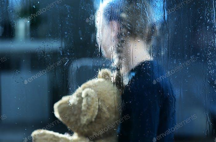 Mädchen mit Teddybär hinter dem Fenster von Regen fallen