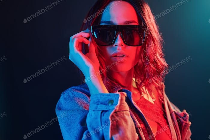 Portrait of young girl in sunglasses in red and blue neon in studio