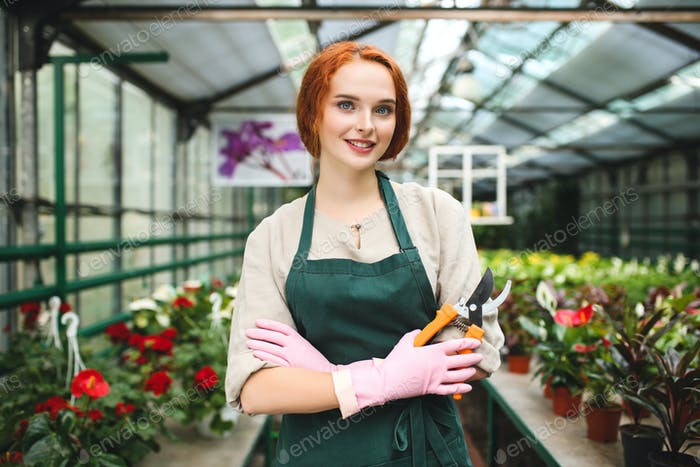 Pretty smiling florist in apron and pink gloves standing with garden scissors in hand