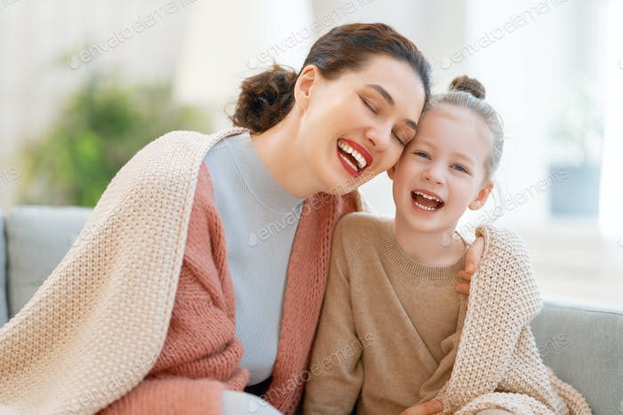 Mom and her daughter smiling and hugging