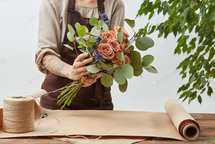 Young woman florist is making bouquet with fresh flowers roses living coral color at the table with