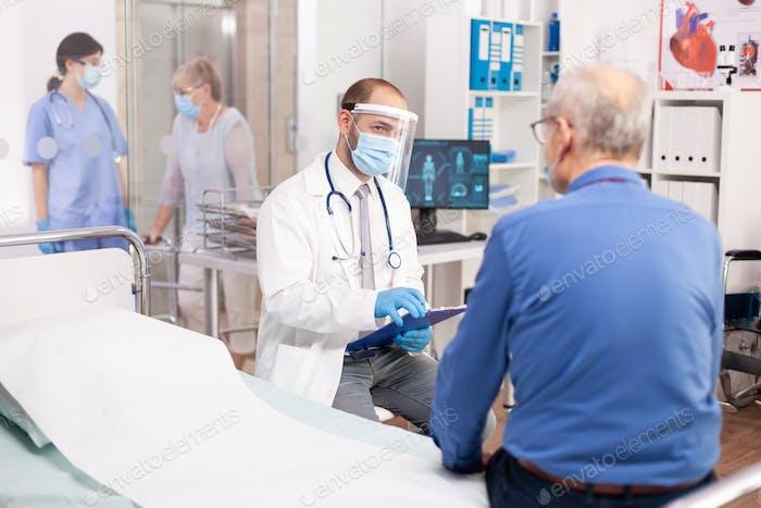 Medical staff questioning senior man in clinic consultation room