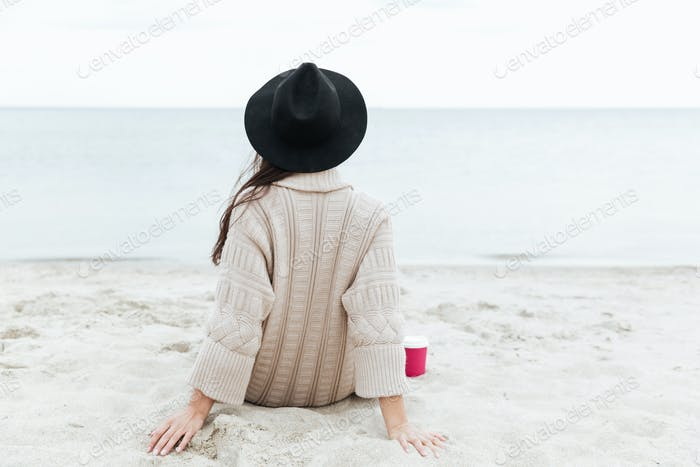 Back view photo of caucasian lady sitting outdoors at beach