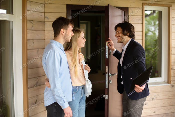 Real estate agent inviting young married couple to enter house for sale