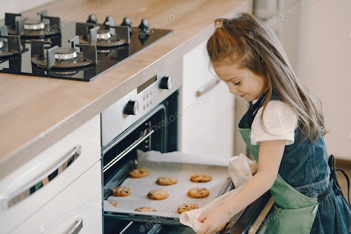 Little girl pulls a cookie from the oven