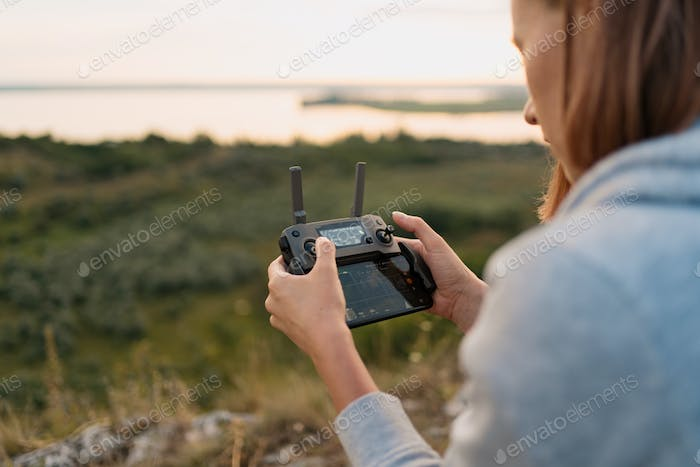 Woman in nature piloting a drone