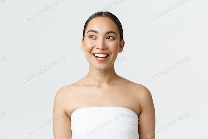 Beauty, cosmetology and spa salon concept. Enthusiastic asian girl with happy smile looking upper