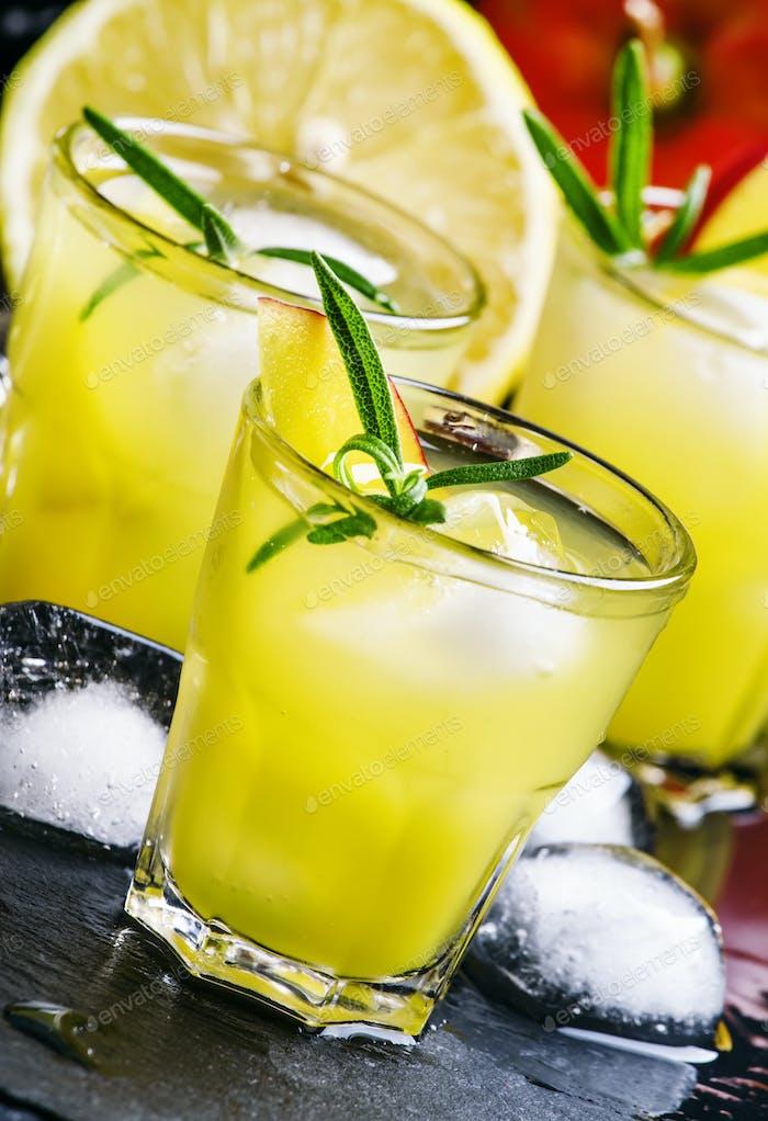 Mango lemonade, with rosemary, lemon juice and ice, black background, selective focus