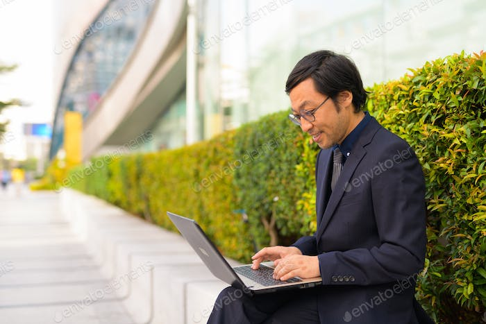 Profile view of happy Asian businessman sitting while using laptop outdoors