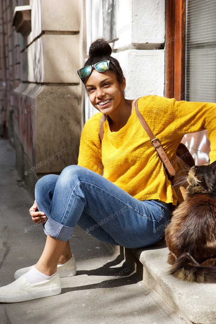 Beautiful young woman sitting by a street with cat