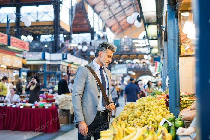 Mature businessman buying fruit in a city.