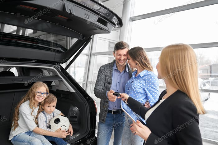 Family buying auto in dealership, manager giving car keys