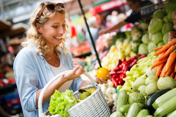 Young woman buying vegetable on stall at the market