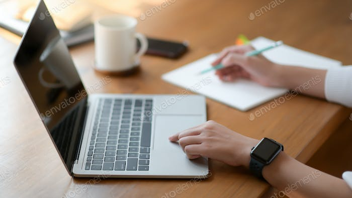 The hand of a young woman using a laptop and writing a report, She works from home.