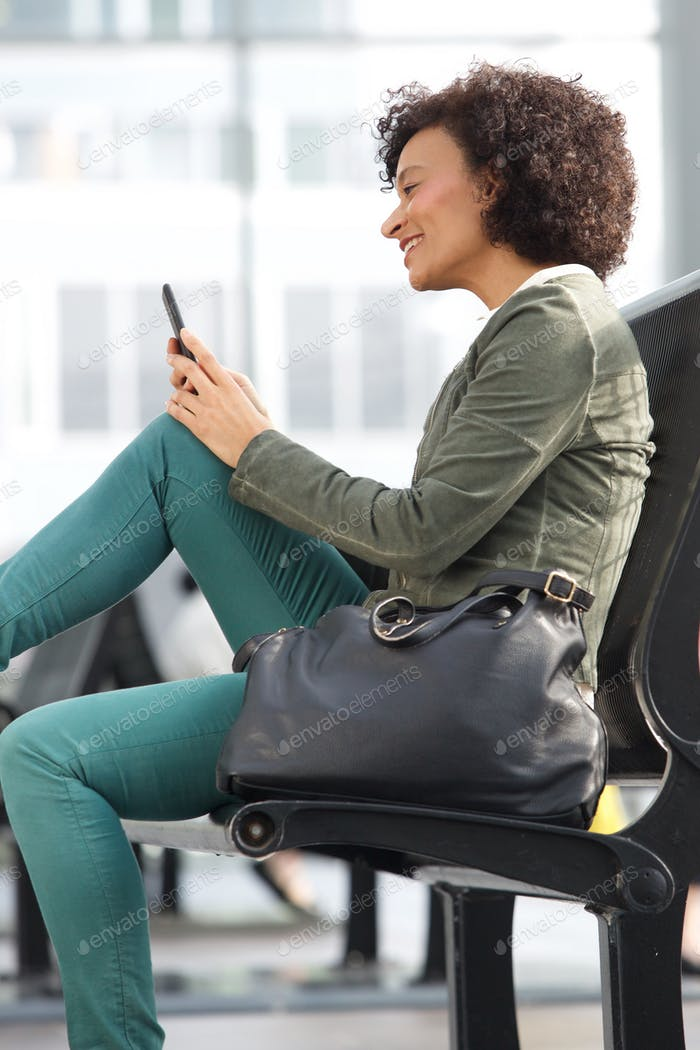 african american woman sitting on bench and looking at mobile phone