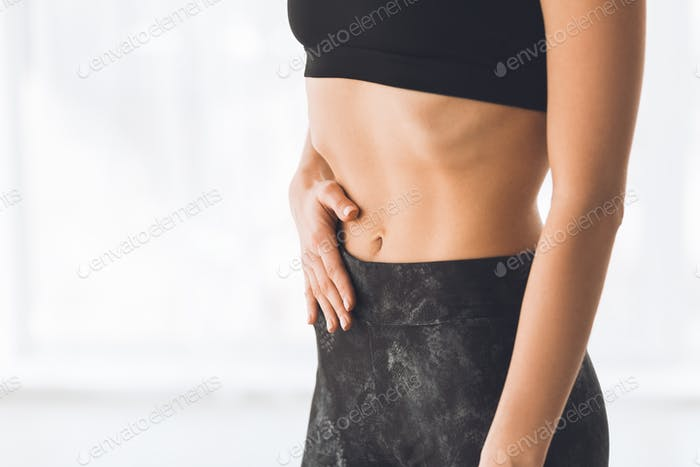 Young woman making exercise on belly vacuum