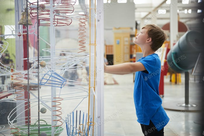 Young boy standing looking at a science exhibit, side view