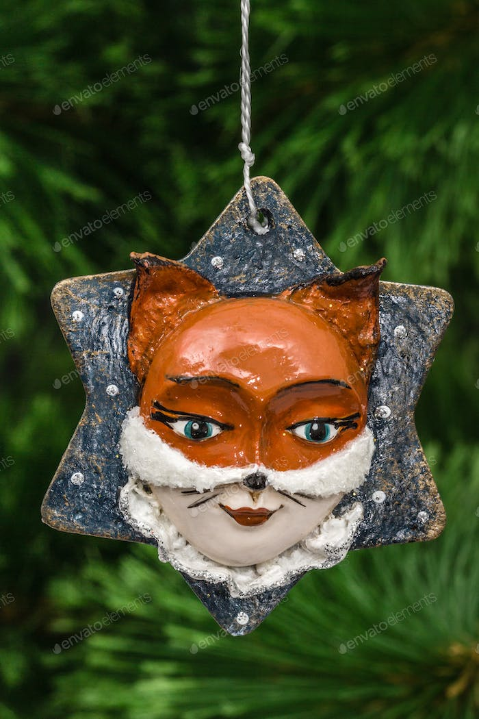 Festive decoration in the shape of a foxy mask, on a Christmas t