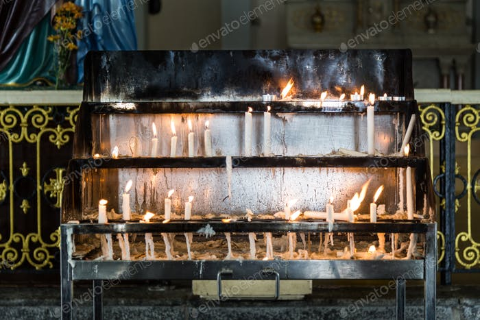 Candles station with burning candles within Catholic church