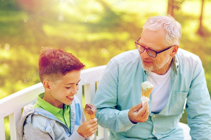 old man and boy eating ice cream at summer park