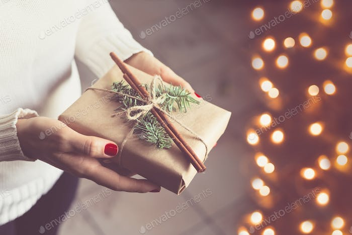 Girl in a winter white warm sweater holds a decorated Christmas gift box.