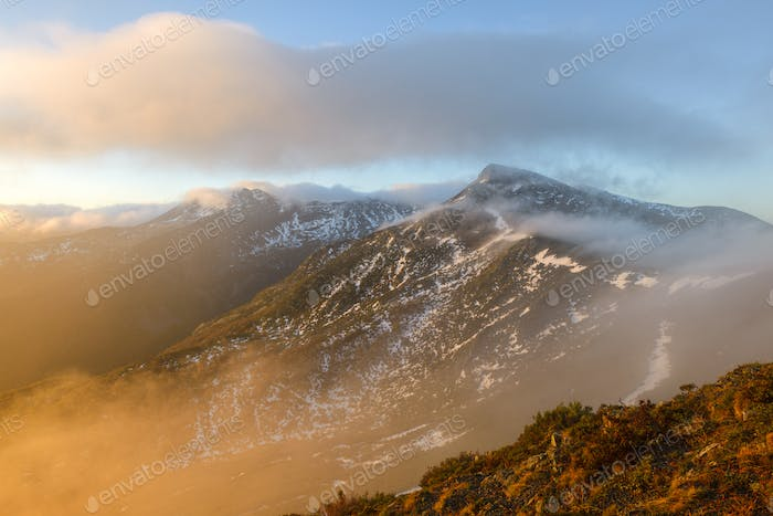 The light of the rising sun clears the mists in the mountains