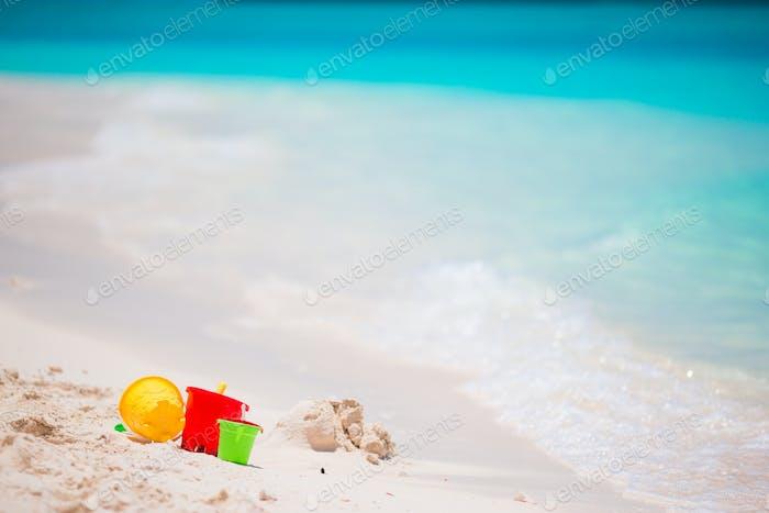 Kids beach toys on white sandy beach background turquiose water