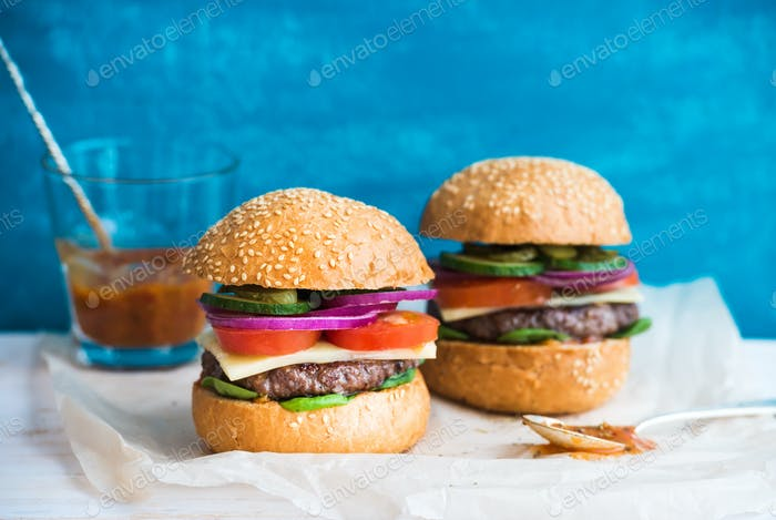 Fresh beef burger with cheese, vegetables and spicy tomato sauce on paper, blue wooden background.