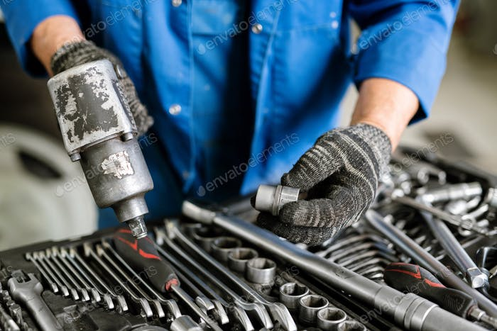 Gloved engineer of contemporary machine repair service with worktool