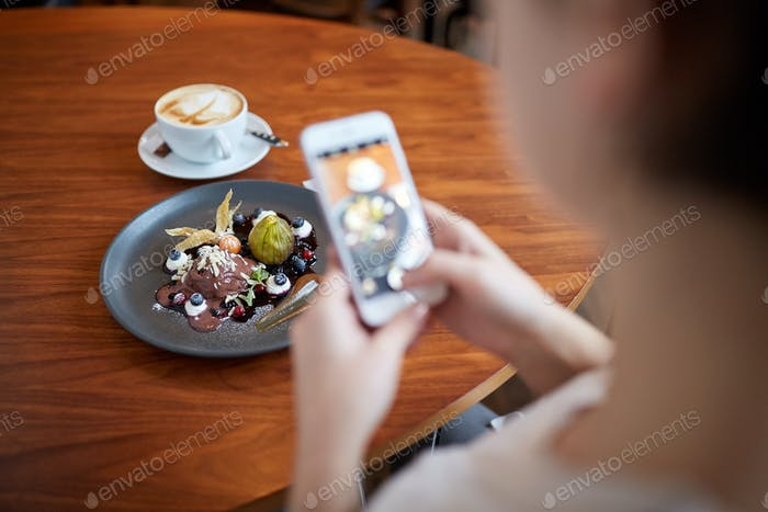 Thumbnail for woman with smartphone photographing food at cafe