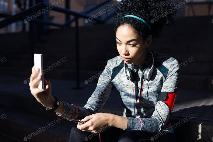 Fit and sporty young woman using her mobile phone.