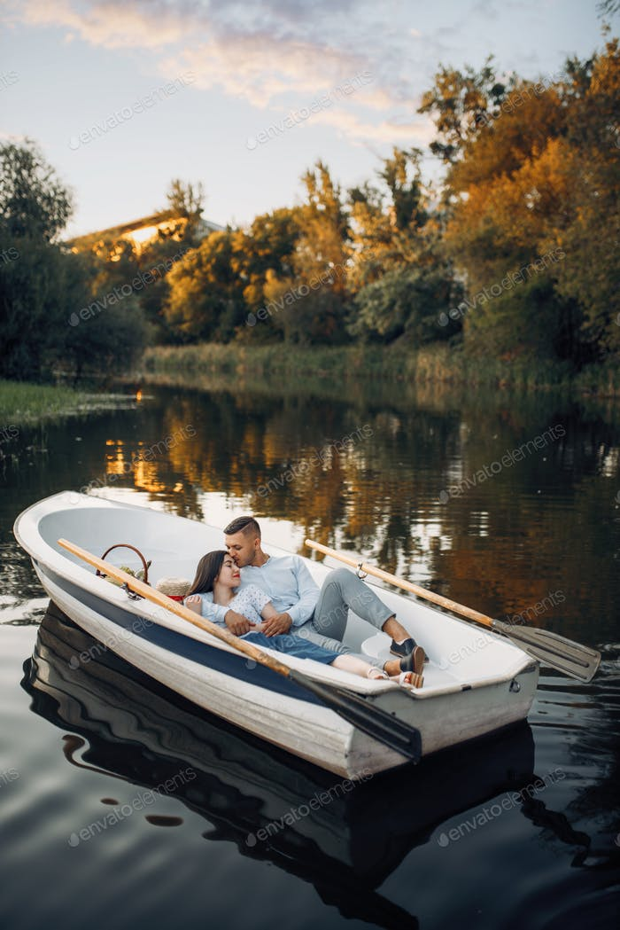 Love couple lying in a boat on lake at sunset