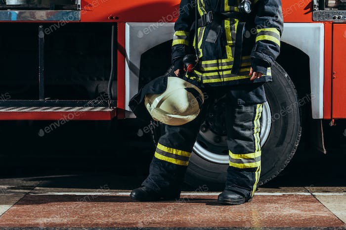 partial view of female firefighter in protective uniform with helmet in hand standing near truck at