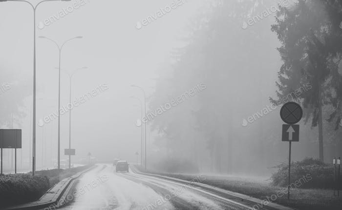 Cars in the fog. Bad weather and dangerous automobile traffic on the road. black and white