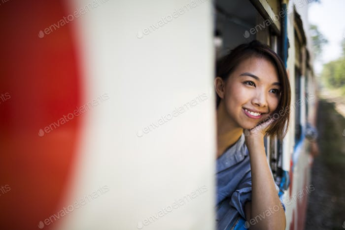 Smiling young woman riding on a train, looking out of window.