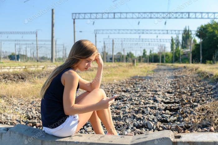Teenager girl with mobile sitting on unfinished rail track