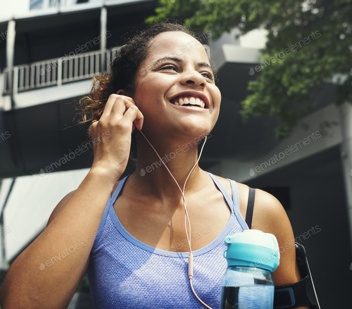 Healthy woman exercising while using technology