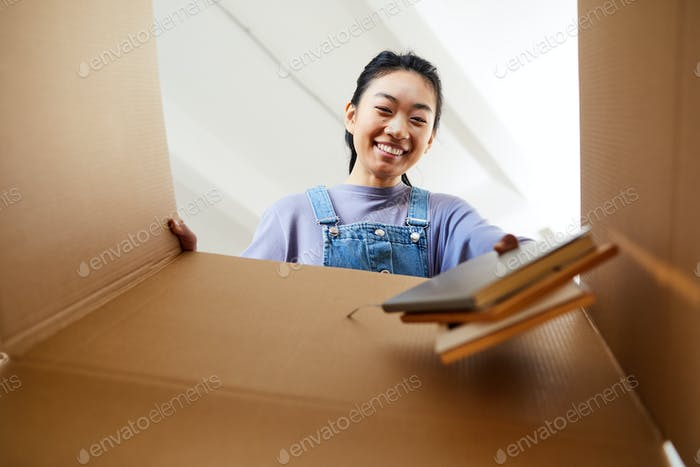 Asian Woman Unpacking Box Low Angle