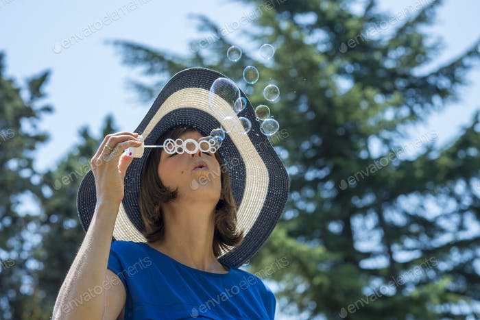 Stylish woman in a straw sunhat blowing bubbles
