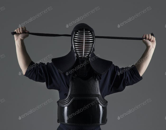 portrait of male in tradition kendo armor putting his helmet and preparing for the fight