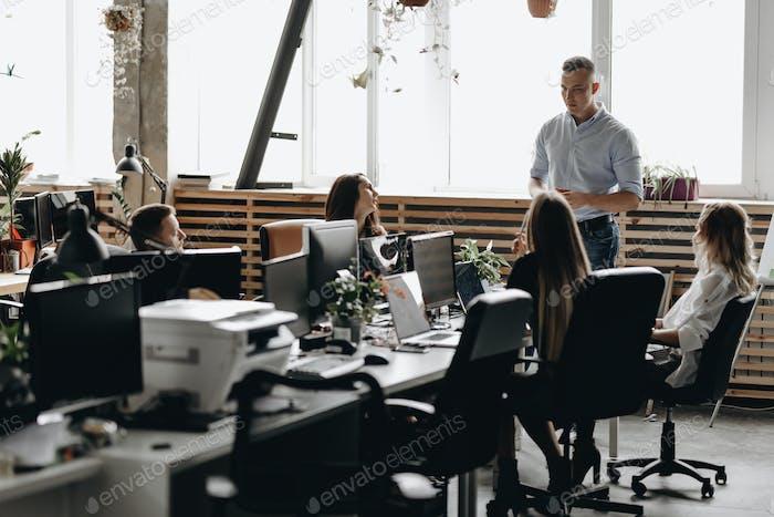 Mitarbeitertreffen eines jungen erfolgreichen Teams im hellen modernen Büro ausgestattet mit modernem Büro