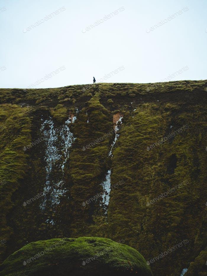 Man on a green ledge walking.