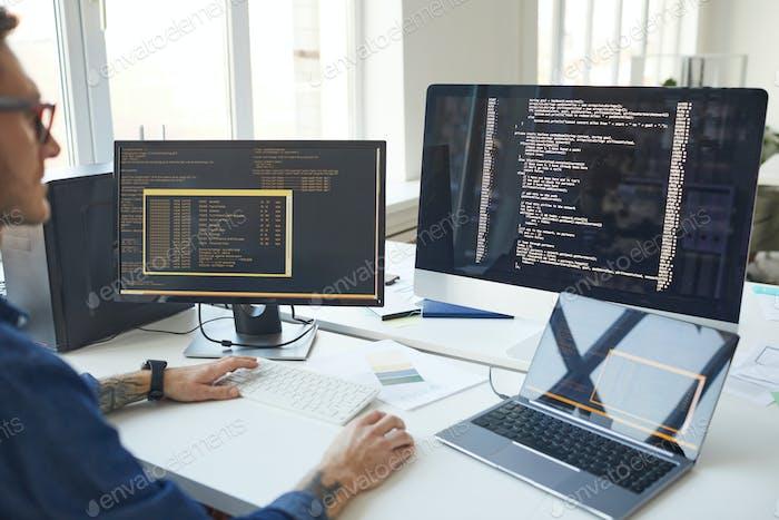 Programador de TI escribiendo código en la pantalla del ordenador