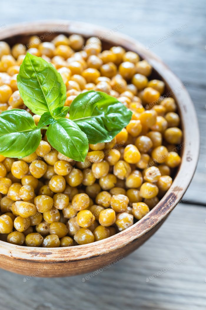 Bowl of roasted chickpeas on the wooden background