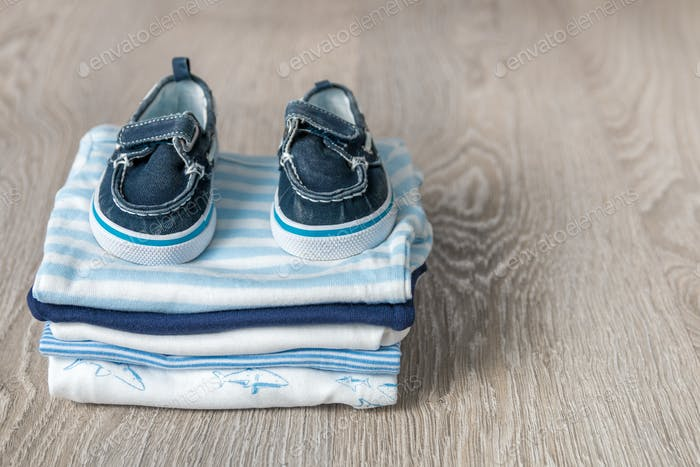 Folded blue and white bodysuit with shoes on it grey wooden background. diaper for newborn boy