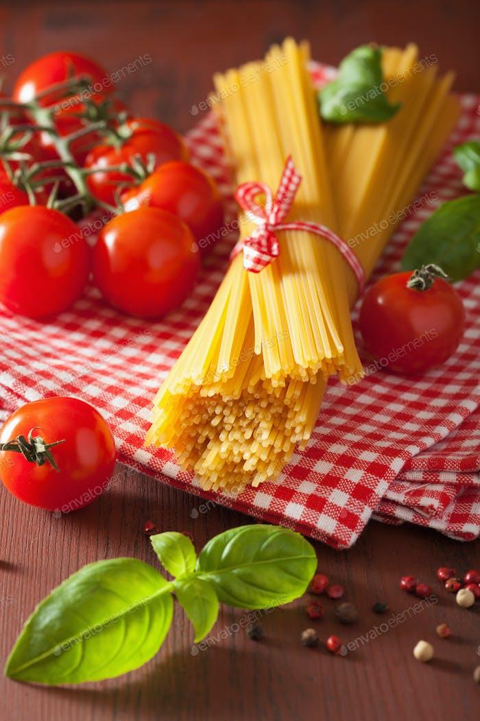 raw spaghetti pasta basil tomatoes. italian cuisine in rustic ki
