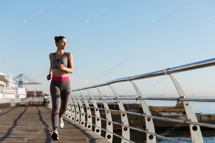 Image of attractive athletic woman in sportswear jogging in the morning, looking at sea and smiling