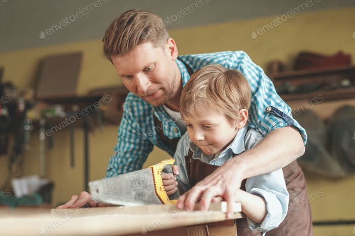 Father and son sawing a plank