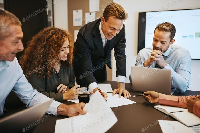 Smiling businesspeople discussing paperwork together in an office boardroom